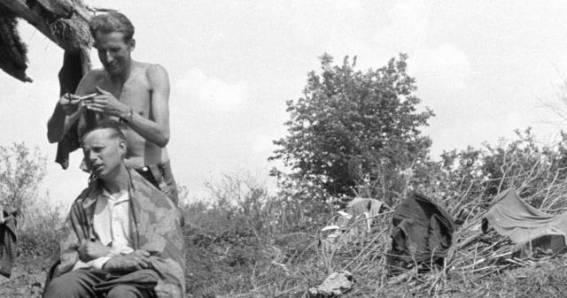 A German Wehrmacht soldier receives a haircut in the field during a pause in hostilities of the Battle of Belgorod.jpg